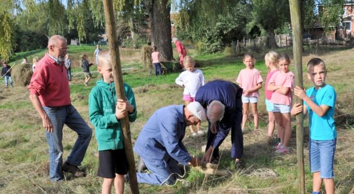 Oude boeren leren kinderen hooien