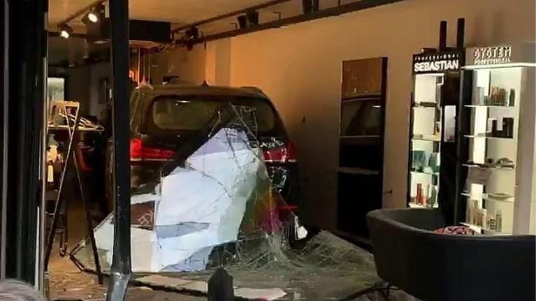 Spectaculair ongeval in drukke winkelstraat: auto belandt in etalage van kapperszaak