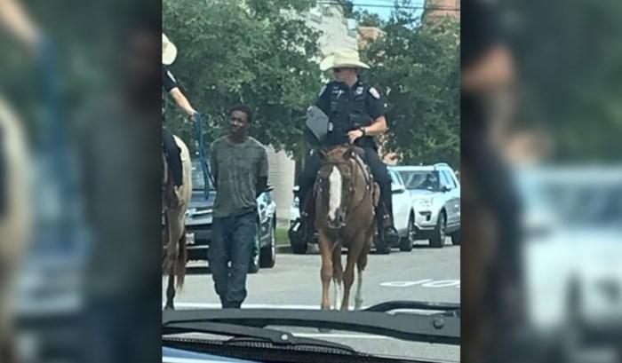 Schokkend beeld: blanke Amerikaanse agenten te paard leiden zwarte arrestant met touw over straat