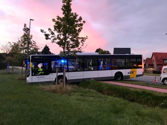 Bus rijdt van de weg, over gracht, in grasveld
