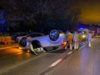 Auto gaat over de kop na botsing: twee gewonden