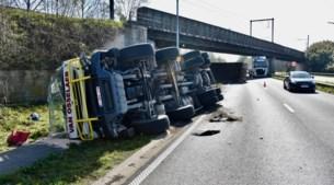 Haakarm met container staat nog omhoog: truck smakt hevig tegen spoorbrug en kantelt