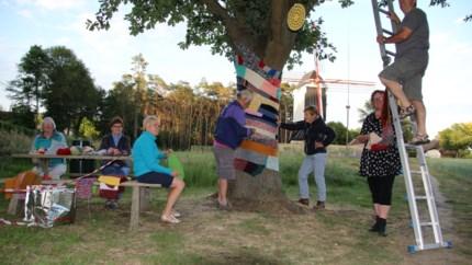 Creatieve dames meten bomen kleurig jasje aan om 100ste verjaardag Ferm te vieren